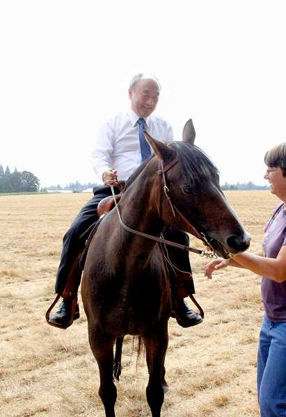 by: LINDSAY KEEFER - Ito Katsumi, mayor of Gosen, Japan, rides a horse at Wooden Shoe Tulip Farm, with the assistance of owner Barb Iverson, during a visit to Woodburn last week.