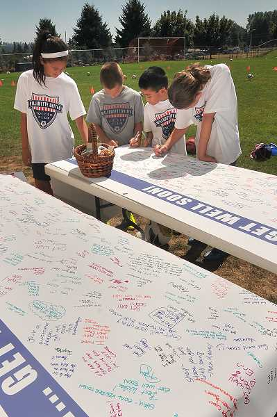 by: VERN UYETAKE - Members of the Willamette United Soccer Club sign banners for the girls during a camp held Aug. 13.