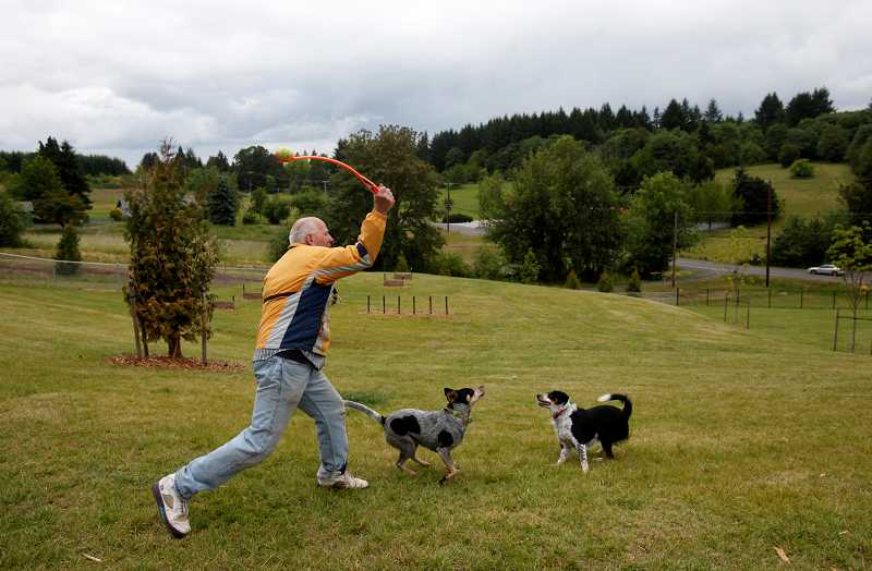 by: TIMES PHOTO: JONATHAN HOUSE - Michael Perry throws a ball to his two dogs Sally and Mya at the Tualatin Hills Park and Recreation Districts new Paul & Verna Winkelman Park near Cooper Mountain.