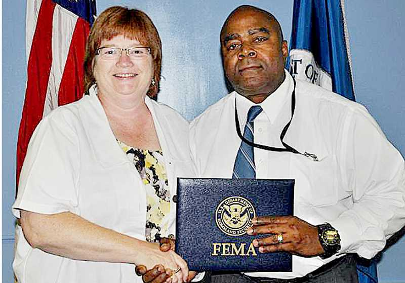 by: SUBMITTED - Pomp and circumstance - Susan Lamb is congratulated by Tony Russell, superintendent of the Federal Emergency Management Agency's Emergency Management Institute, after graduating from the institute in July.