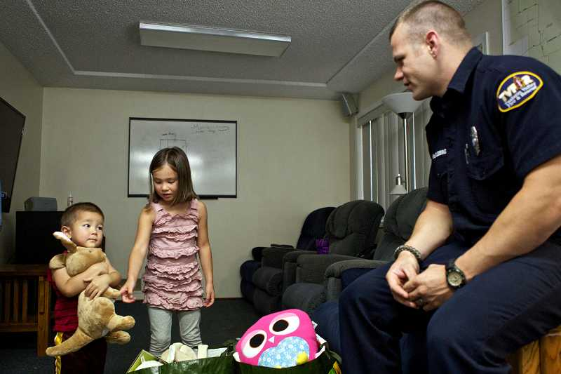 by: TIMES PHOTO: JAIME VALDEZ - Two-year-old Jackson Ditchfield is unsure whether he wants to give up a stuffed animal that his older sister, Giselle, got for her sixth birthday.