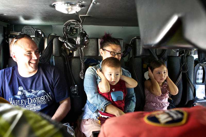 by: TIMES PHOTO: JAIME VALDEZ - Rod and Valerie Ditchfield of Beaverton sit in the backseat of a TVF&R fire engine with their kids, Jackson, 2, and Giselle, 6, who are seen protecting their ears from the noise of a siren.