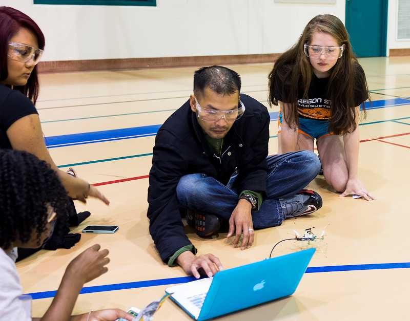 by: TIMES PHOTO: CHASE ALLGOOD - From left, Ovania Mosley, Christian Lee, Khang Nguyen and Erica Lipski tweak the programming on their quad copter robot at the Ultimate Engineering Experience on Tuesday morning at Portland Community College's Rock Creek campus.