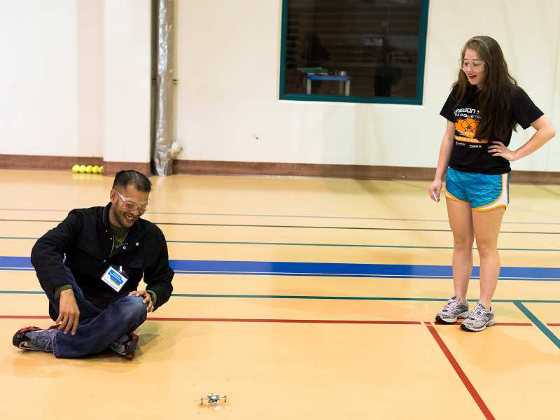 by: TIMES PHOTO: CHASE ALLGOOD - Khang Nguyen and Erica Lipski laugh as their quad copter robot attempts to take flight at the Ultimate Engineering Experience camp on Tuesday morning at Portland Community College's Rock Creek campus.