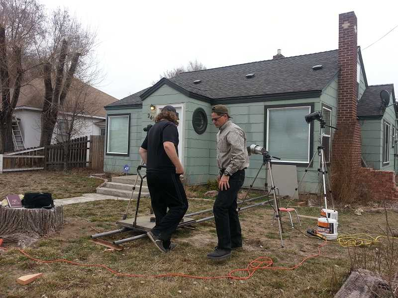 Torrey Rogers, left, and Duke White set up equipment to shoot a scene outside the Rogers' home in Madras.