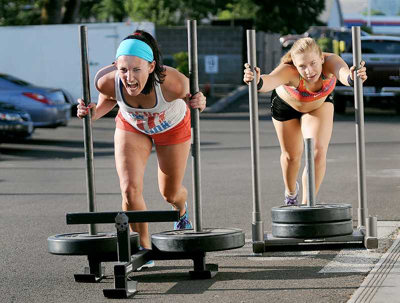by: SETH GORDON - Fit is as fit does - Newberg CrossFit members AnnaLissa Amaya (left) and Bethany Quist push sleds as part of their workout Monday.