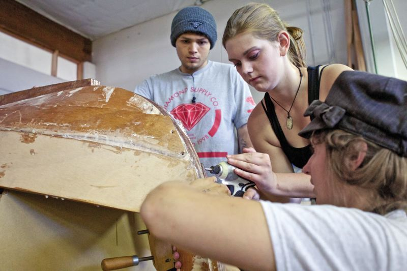 by: TRIBUNE PHOTO: JAIME VALDEZ - Hannah Lynch, right, a boat builder instructor, assists Savannah Weber, 17, a student at Rosemary Anderson High School, as she screws in a wooden strake on a sail boat. Owen Mitchell, 17, a student at Mt. Hood Community College, helps.