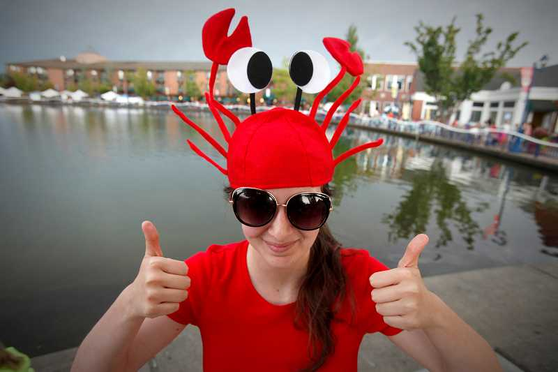 by: TIMES PHOTO': JONATHAN HOUSE - Erin Carmona gets into the spirit of the Tualatin Crawfish Festival on Friday night. The Chamber of Commerce is looking for someone to take over the 65th-year-old festival. If a sponsor isn't found, this could be the last Crawfish Festival the city has.
