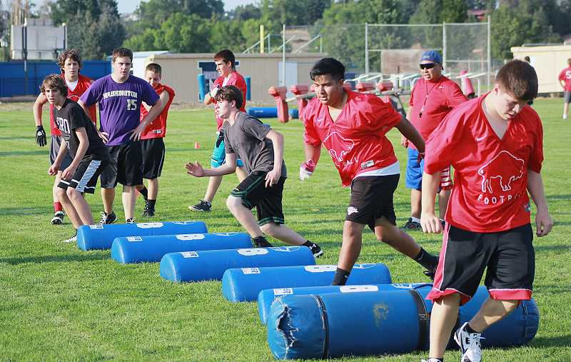 by: BILLY GATES/THE PIONEER - Potential Madras High School linebackers run through agility drills during the teams football camp Monday at Madras High School.