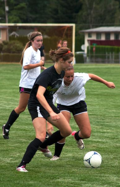 by: JOHN WILLIAM HOWARD - Lucy Davidson, at left in black, fights for possession of the ball during a intrasquad scrimmage between Scappoose and St. Helens high school on Wednesday, Aug. 14. Davidson commutes 25 minutes to play soccer on the campus of the University of Portland.