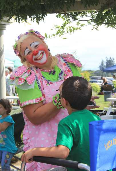by: NIKKI DEBUSE - The sixth annual Firehouse Cook-Off at Wooden Shoe Tulip Farm hosted 12 teams Saturday. Lotta the Clown offers facepainting for younger guests.