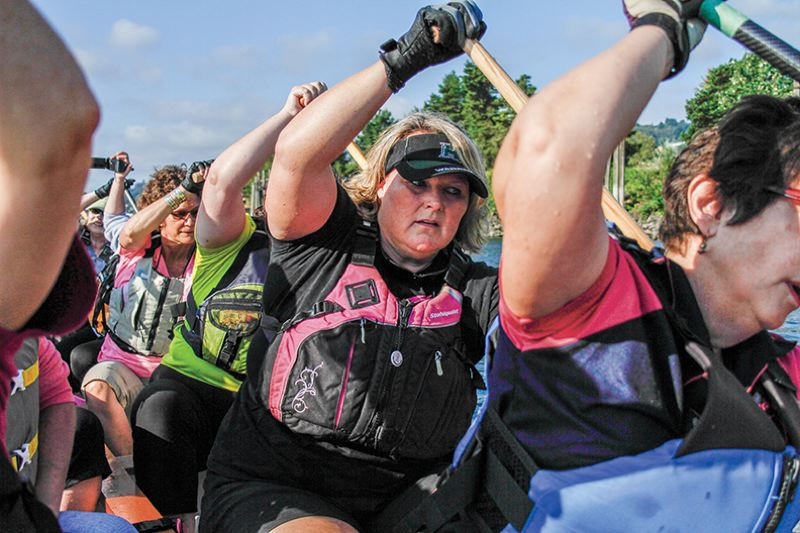 by: NEWS-TIMES PHOTO: AMANDA MILES - Forest Grove resident and breast cancer survivor Karen Holscher (center) paddles with the Pink Phoenix Dragon Boat Team during a practice session on Saturday morning.