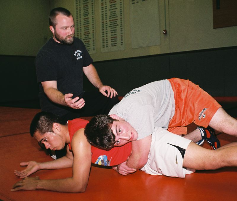 by: JOHN DENNY - Gladstone wrestling coach Michael Hess works with Logan Good (on top) and David Ventura during a summer freestyle workout.