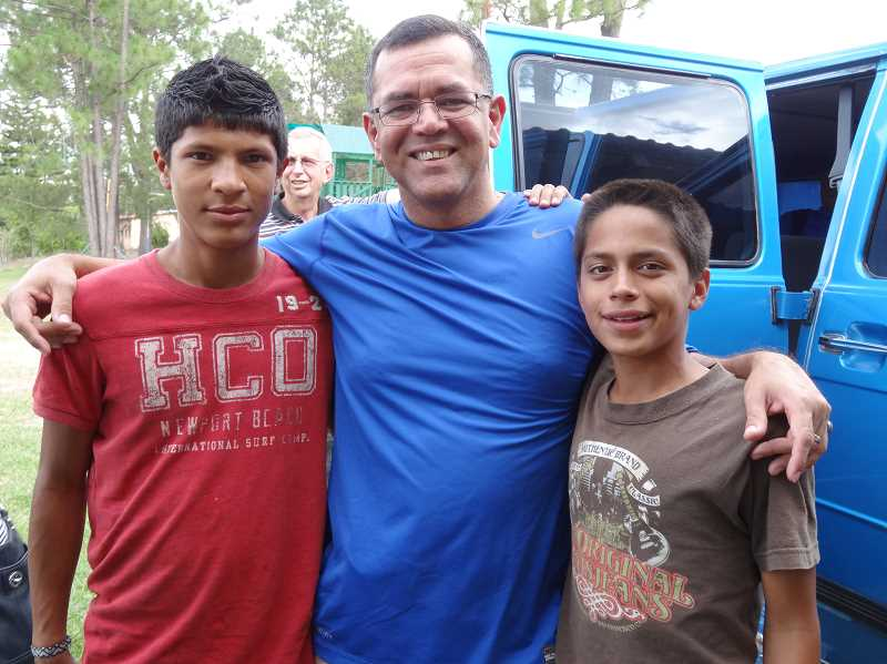 by: COURTESY OF WOODBURN FOURSQUARE CHURCH - Pastor Luis Molina shares a moment with two young men living at the Didasco Children's Home in Honduras.