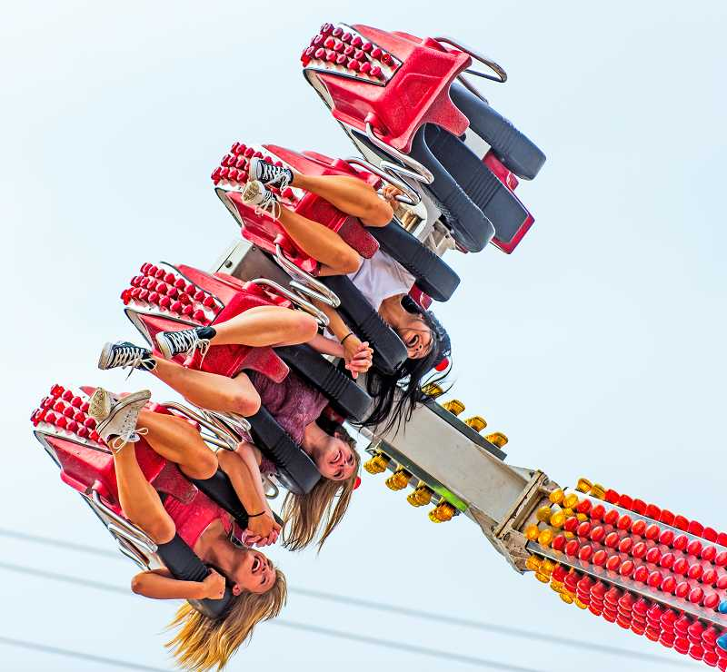 by: RAY HUGHEY - Three fairgoers get an upside down look at the midway at the 2013 Clackamas County Fair.