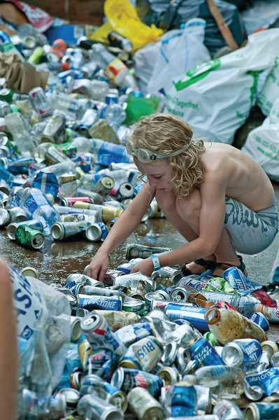 by:  MARK GAMBA - A boy sorts through beer cans at last year's Clackamas River clean-up activity.