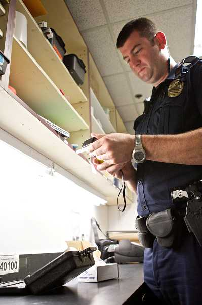 by: TIMES PHOTO: JAIME VALDEZ - Beaverton Police Department Officer Sean Hinkley prepares a breathalyzer kit before heading out on patrol.