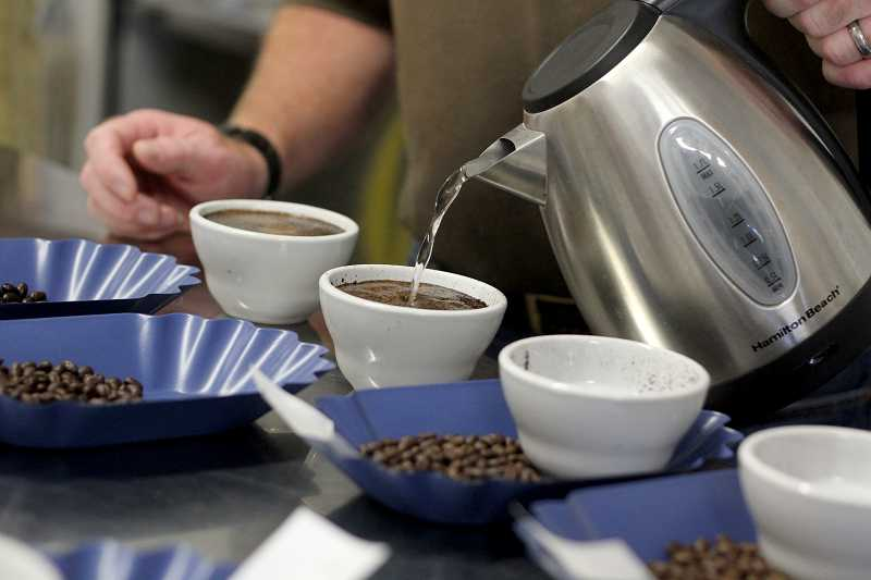 by: TIMES PHOTO: JONATHAN HOUSE - Erik Knudsen, coffee steward at Dovetail Coffee Roasters, tests different brews during a cupping at the roasting facility on Southwest Nimbus Avenue in Beaverton.