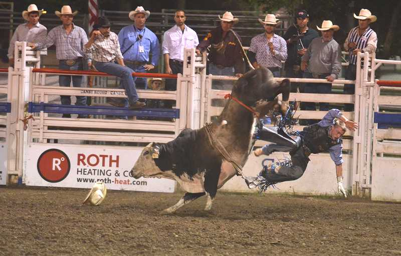 by: JEFF GOODMAN - Bull rider Dakota Beck gets tossed before the 8-second mark Aug. 13 at the 56th-annual Canby Rodeo. Only two competitors posted scores in the bull-riding competition that night.