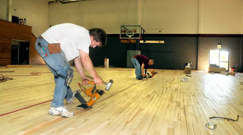 by: SETH GORDON - From the floor up - A Game Courts, LLC, employees William Tracey, of Silverton, and Joe Miller, of Salem, nail the boards that together will make up C.S. Lewis Academy's new gymnasium floor at the former Open Bible Christian School campus Monday morning. The two schools merged this year.