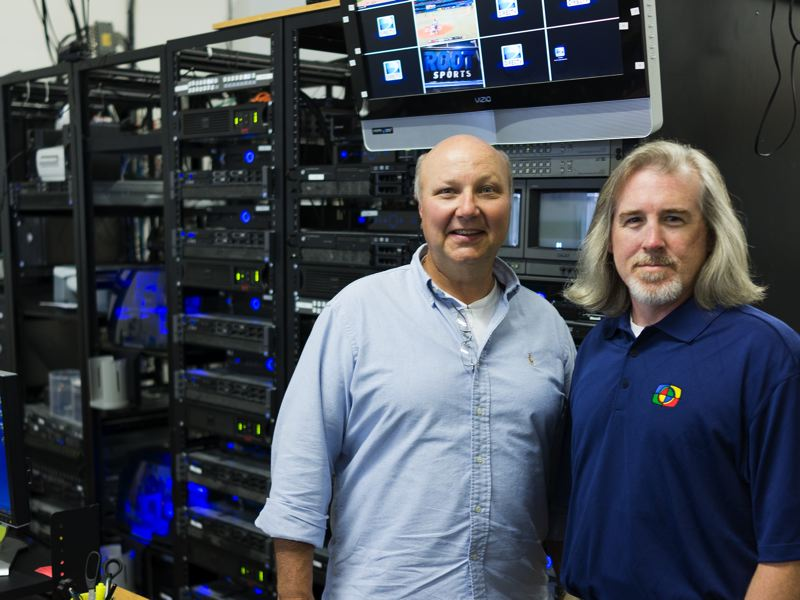 by: HILLSBORO TRIBUNE PHOTO: CHASE ALLGOOD - Ken Rhodes (left) and Mark Watson (right) stand in front of rackmount sercvers and various other computer equipment they use to capture, edit, and deliver game footage for their clients.