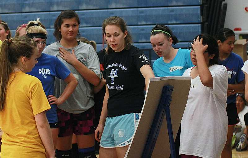 by: BILLY GATES/THE PIONEER - First-year head coach Rhea Cardwell (center) goes over a performance chart with the Madras High School volleyball team during Monday's practice at Madras High School.