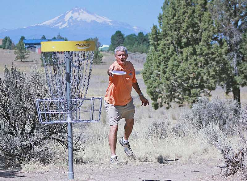by: BILLY GATES/THE PIONEER - Larry Kirk tries to finish out a hole at the disc golf course at Juniper Hills Park in Madras on Wednesday. Kirk, 52, is making his third tour around the United States to play disc golf in all 50 states in 50 days, in an effort to help promote the game of disc golf.