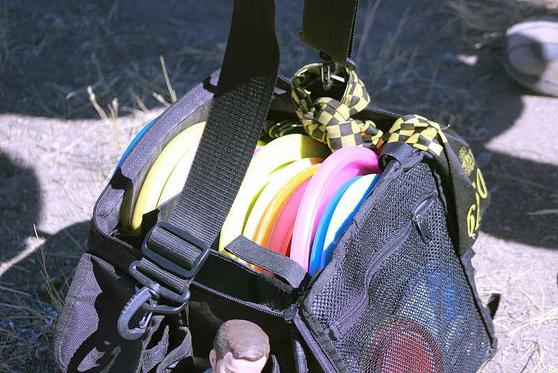 by: BILLY GATES/THE PIONEER - Disc golfers use a variety of different discs for different situations, as evident by Larry Kirk's full bag of discs he carries with him.
