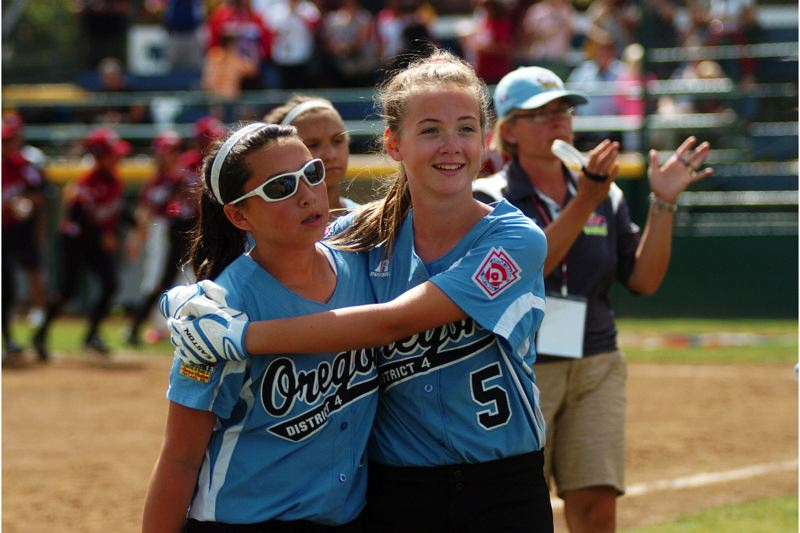 by: DAN BROOD - HAPPY HUG -- Tualatin City's Elizabeth Hillier (right) smiles as she hugs teammate Lily Marshall following the seventh-place game at the Little League Softball World Series.