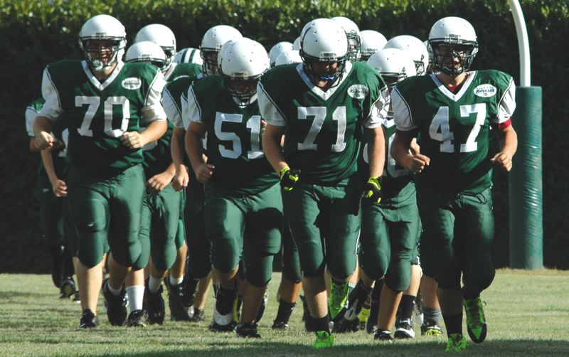 by: ESTACADA NEWS: PARKER LEE - Estacada players rush onto the field before Saturdays intrasquad scrimmage.