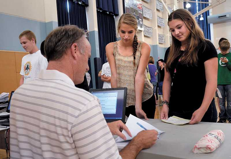 by: PAMPLIN MEDIA GROUP: VERN UYETAKE - WHS Assistant Principal Dennis Burke helps Alex Gowen, right, and Toni Gowen register to participate in athletics.