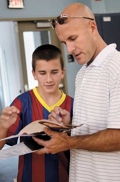 by: PAMPLIN MEDIA GROUP: VERN UYETAKE - Calvin, left, and his dad, Scott Lucas, decide what photo package to choose.
