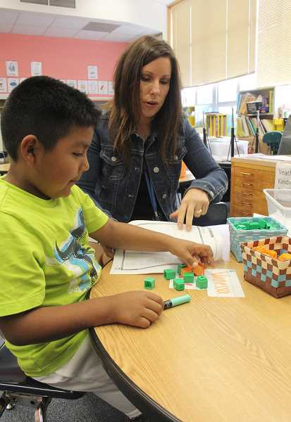 by: LINDSAY KEEFER - Teacher Lynne Koenig helps first-grader Daniel Ceja with counting blocks during Washington Elementary School's summer academy, which wrapped up last week.