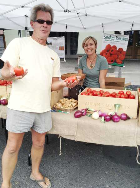 by: COURTESY PHOTO - Charlie Harris of Flamingo Ridge Farm in Gaston and sales assistant Brooke Miller sell Oregon Star tomatoes at the Forest Grove Farmers Market.