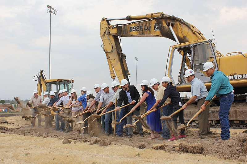 by: SUSAN MATHENY - Construction, community and school district representatives toss dirt at the Aug. 22, groundbreaking for Madras High School's performing arts/sports center.