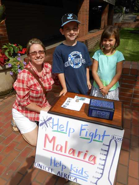 by: REVIEW PHOTO: CLIFF NEWELL - Anna Inustrial was on hand to support her son, Gio, and daughter, Emma, when they set up a table outside of the Lake Oswego Public Library to raise money to help kids in Africa.