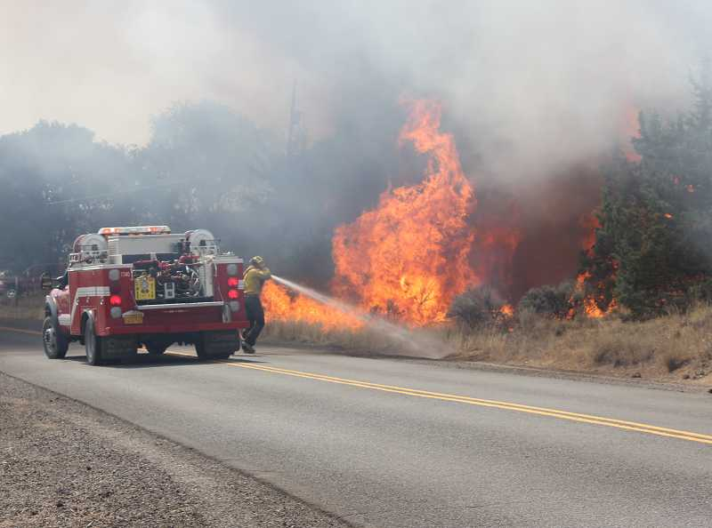 by: SUSAN MATHENY - Firefighters spray flaming junipers and sagebrush on Meadowlark Lane.