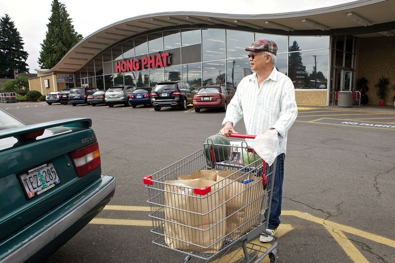 by: TRIBUNE PHOTO: JAIME VALDEZ - Quy Pham of Southeast Portland pushes a cartful of groceries to his car at the new Hong Phat store on 82nd Avenue near Burnside Street. It's one of two large Asian groceries on 82nd Avenue.
