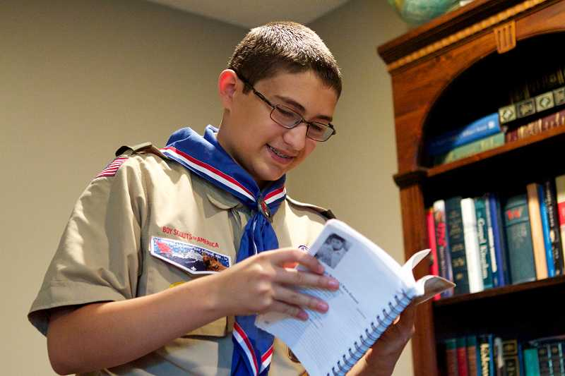 by: TIMES PHOTO: JAIME VALDEZ - George Christensen checks his Boy Scout manual well worn after years of use. The book lists the requirements for all 132 merit badges. George, 15, has earned them all, and then some.