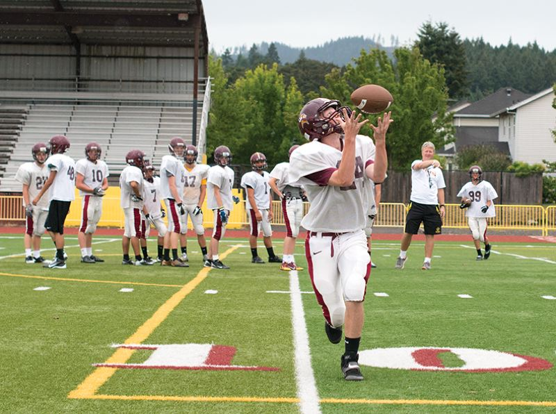 by: NEWS-TIMES PHOTO: CHASE ALLGOOD - Forest Grove football coach Greg Evers throws passes to Viking players on Monday as the team prepares for its season opener this week.
