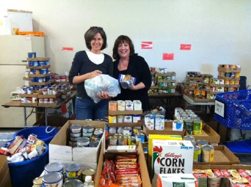 by: SUBMITTED PHOTO - Miller Insurance employees Leslie Thomas and Karen Decker volunteer at the Tualatin School House Pantry. Their company helped the organization secure a $10,000 grant.