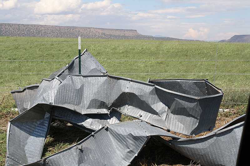 by: STEVE KEEVER - A grain silo, owned by Paul and Louann Cowsill, of Gateway, was blown apart and scattered by the force of the storm on Sunday. The crumpled metal was located on Northeast McFarlane Lane.