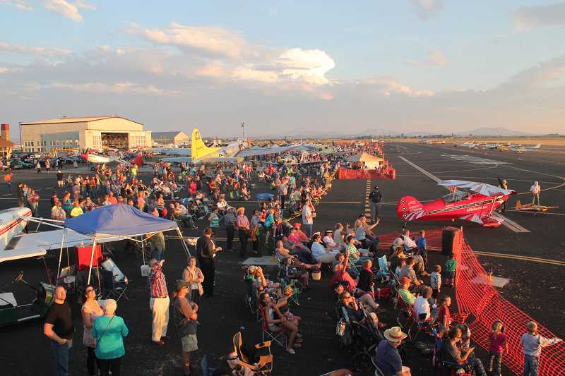 by: HOLLY M. GILL - The crowd focuses on an aerial performance on Friday evening at the Airshow of the Cascades. Attendance on Friday was up 25 percent over last year.