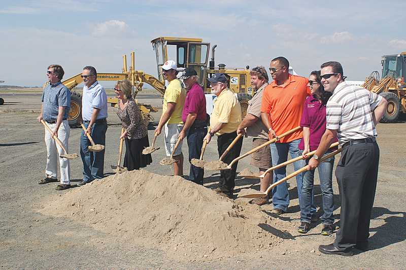 by: HOLLY M. GILL - With the shovel honors for Friday's groundbreaking were, from left, county commissioners Mike Ahern and John Hatfield, EDCO's County Director Janet Brown, Madras city council members Jim Leach, Tom Brown, Royce Embanks, Airport Manager Rob Berg, Museum Manager Mike Oliver, Madras Mayor Melanie Widmer and Community Development Department Director Nick Snead.