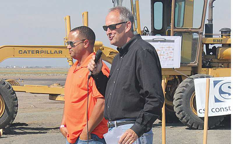 by: HOLLY M. GILL - Steve Thomas, right, president of the Erickson Group, and Mike Oliver, general manager of the Tillamook Naval Air Station Museum, each addressed the crowd at the groundbreaking.