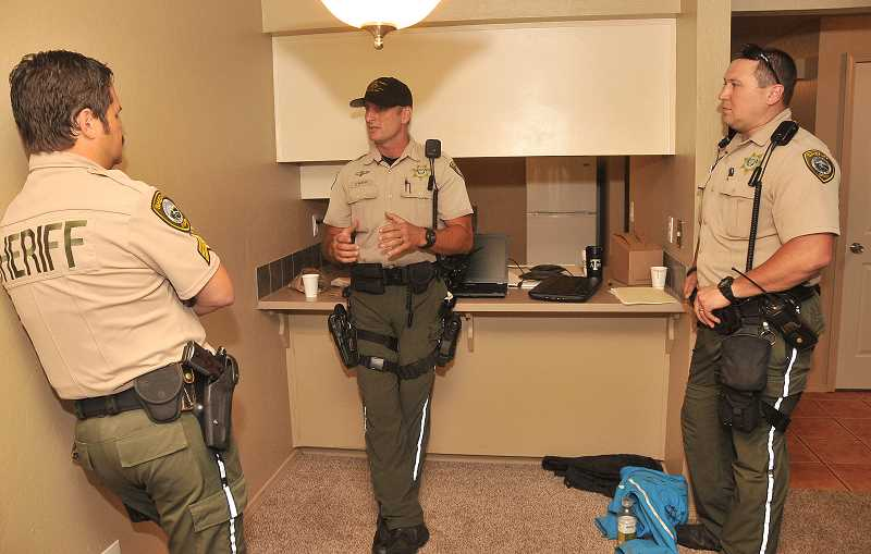 by: REVIEW PHOTO: VERN UYETAKE  - Sgt. John Naccarato (facing away) discusses the undercover operation with sheriffs Dep. Robby Nashif (center) and Dep. Bryan Morris.