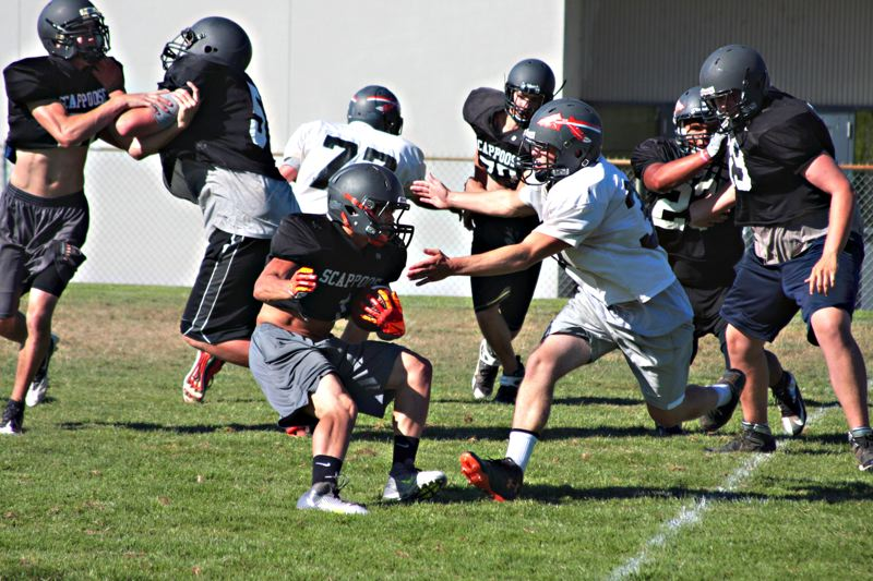 by: JOHN WILLIAM HOWARD - Carson Davison spins around a defender at practice last week. Davison's speed and ability to get to the edge will be a huge asset in the match up with Roosevelt, where the Indians need to spread out the big defensive line and wear them down by moving laterally.