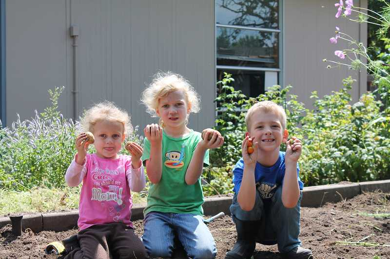 by: TIDINGS PHOTO: KATE HOOTS - Claire Allen, center, her sister, Madeline, 4, and neighbor Kelan Goodrich, 5, help out at a volunteer workday  Aug. 3.