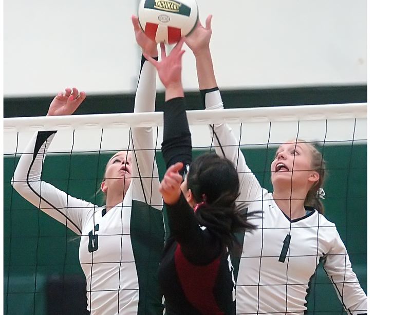 by: DAN BROOD - DOUBLE TEAM -- Tigard's Michelle Simmons (left) and Lindsey Rosette (1) go up together for a block in a match last year. Simmons and Rosette both are back for their season season with the Tigers.
