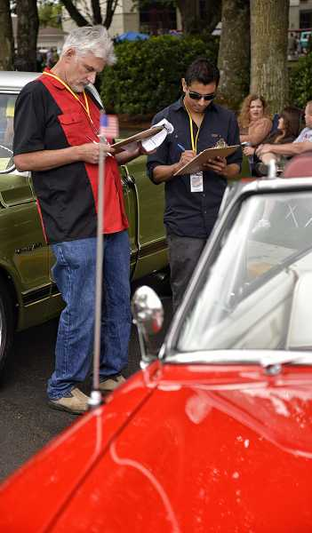 by: RAY HUGHEY - Judges Charlie Watkins, left, and Carlos Cuevas check out an entry in the classic car show.